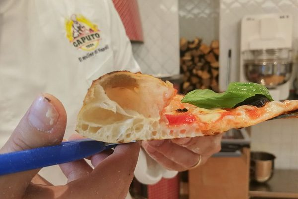 Slice of pizza held by a chef