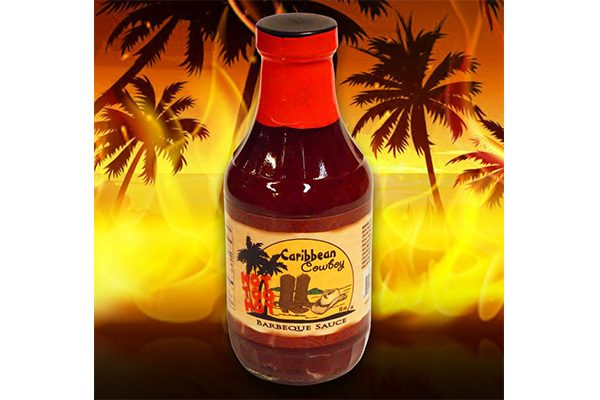 Retail bottle of Caribbean Cowboy barbeque sauce on a firey background