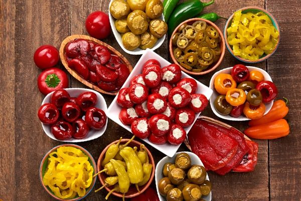 Assorted cherry, banana and jalapeno peppers on a wood table