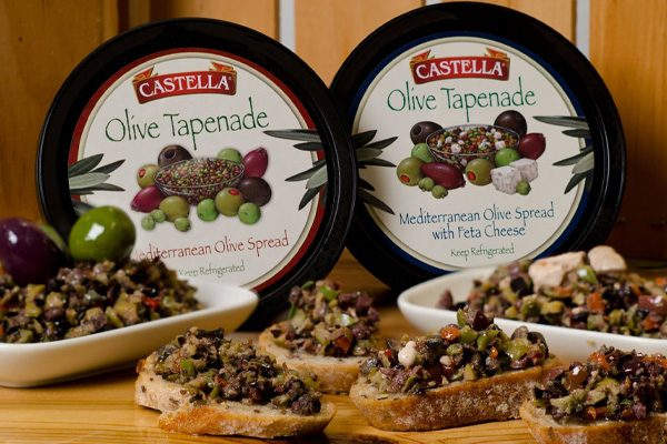 Castella Olive Tapenade containers next to bruschetta topped with the olive tapenade