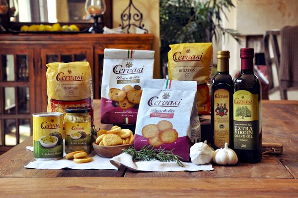 Retail packages of Cervasi pasta, artichokes, bruschetta, vinegar and olive oil on a brown table