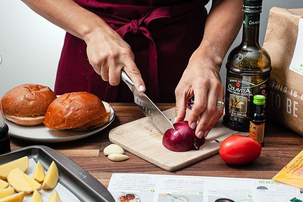 Person slicing a red onion next to hamburger buns and uncooked fries with Colavita Extra Virgin Olive Oil