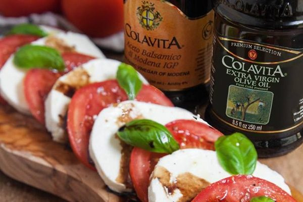Caprese salad next to bottles of Colavita Balsamic Vinegar of Modena and Extra Vigin Olive Oil