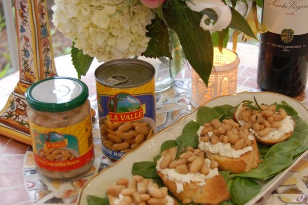 White cannellini beans in retail jars by bruschetta topped with the beans