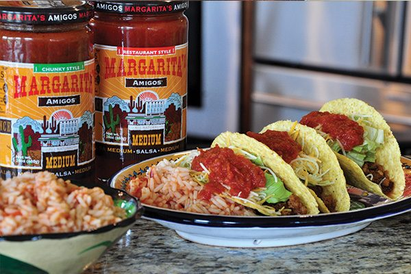 Plate of three tacos with Margarita's Amigos salsa jars in the background