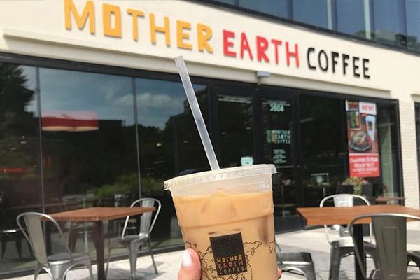 Iced latte being held outside in front of a Mother Earth Coffee shop location