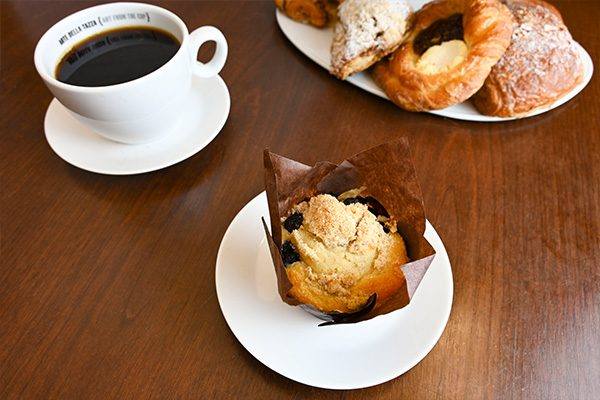 A muffin and cup of coffee with a plate of other assorted pastries in the background