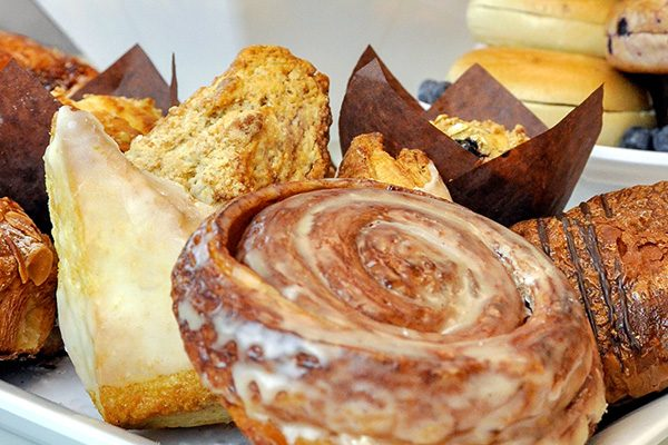 Close up of a pastry tray with scones, cinnamon rolls, muffins and croissants made by Parisi Kitchens