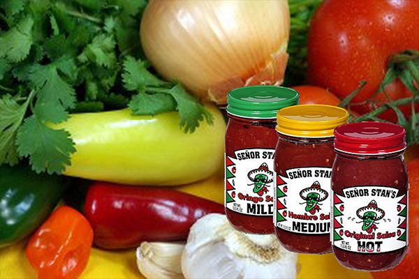 Senor Stan's salsa jars against an image of vegetables