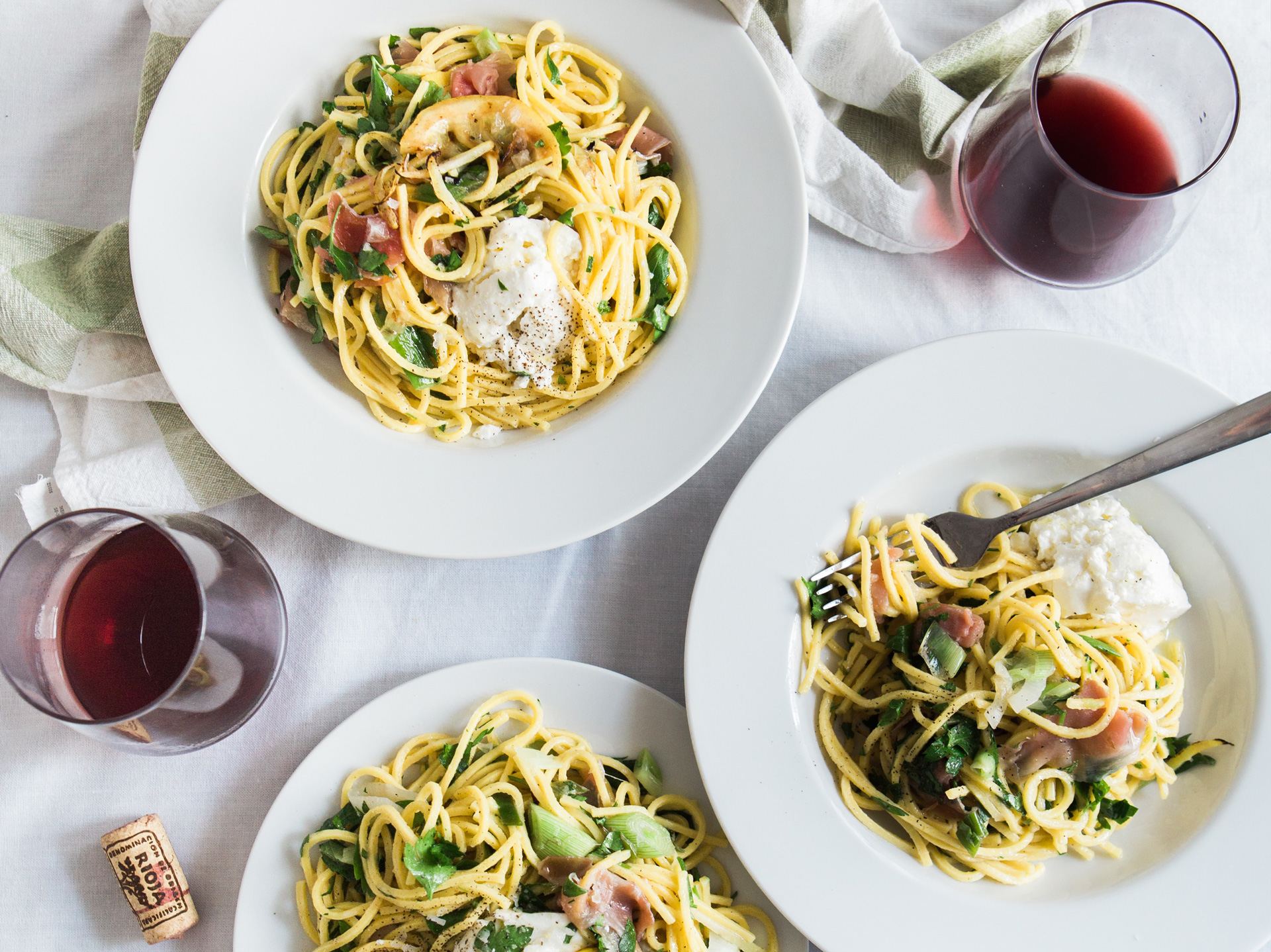 Three plates of a pasta dish on a white table cloth with two glasses of red wine